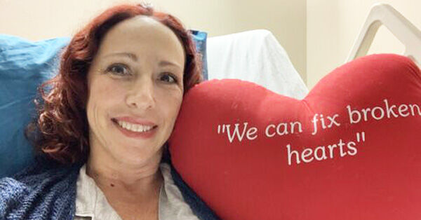 Heart Surgery Patient Smiling with Red Pillow